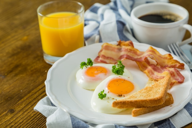 American breakfast with sunny side up eggs, bacon, toast, pancakes, coffee and juice