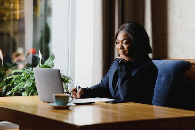 Американская деловая женщина, использующая компьютер в офисе
