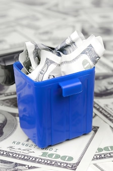 American cash notes are thrown into the trash bin on a multitude of hundred dollar bills