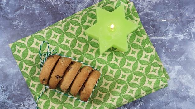 녹색 냅킨과 촛불에 실로 묶인 스택의 미국 초콜릿 칩 쿠키. 초콜릿 칩을 곁들인 전통적인 둥근 바삭바삭한 반죽. 빵집. 맛있는 디저트, 파이.