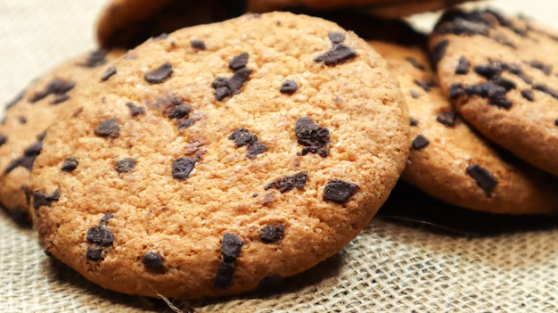 茶色の木製テーブルとリネンナプキンのクローズアップにアメリカンチョコレートチップクッキー。チョコレートチップを使った伝統的な丸みを帯びたカリカリ生地。ベーカリー。おいしいデザート、ペストリー。田舎の静物。
