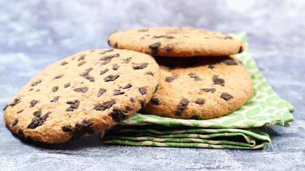회색 배경에 녹색 냅킨에 미국 초콜릿 칩 쿠키. 초콜릿 칩을 곁들인 전통적인 원형 바삭한 반죽. 빵집. 맛있는 디저트, 파이.