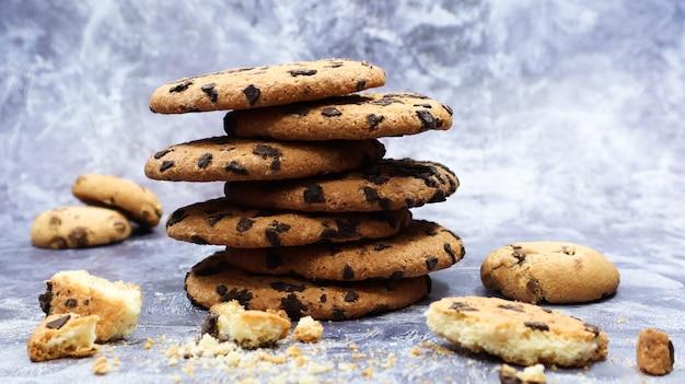 아름다운 회색 대리석 배경에 미국 초콜릿 칩 쿠키가 서로 겹쳐져 있습니다. 초콜릿 칩을 곁들인 전통적인 둥근 바삭바삭한 반죽. 빵집. 맛있는 디저트, 파이.