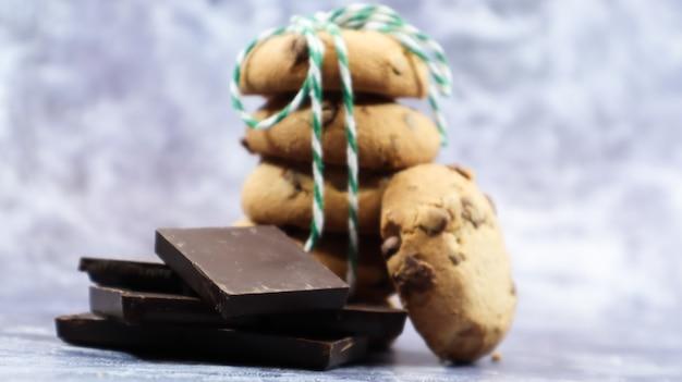 미국 초콜릿 칩 쿠키는 회색 배경에 녹색 실로 쌓여 있습니다. 초콜릿 칩을 곁들인 전통적인 둥근 바삭바삭한 반죽. 빵집. 맛있는 디저트, 파이.