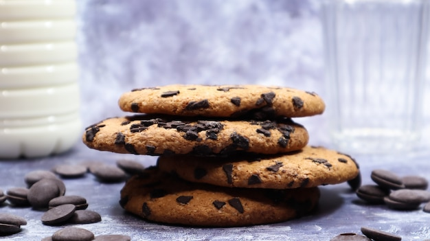 회색 배경에 유리에 우유와 함께 미국 초콜릿 칩 쿠키가 서로 위에 쌓여 있습니다. 초콜릿 칩을 곁들인 전통적인 둥근 바삭바삭한 반죽. 빵집. 맛있는 디저트, 파이.