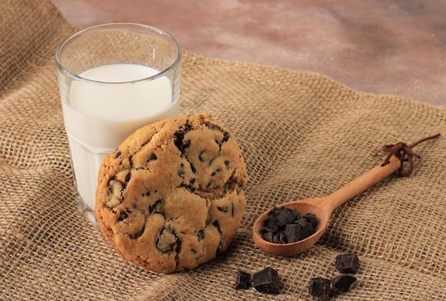 미국 초콜릿 칩 쿠키, 갈색 배경에 신선한 우유 한 잔과 함께 제공되는 부드러운 쿠키
