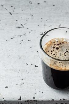 Американский кофе в стеклянной чашке на старый белый деревянный стол.