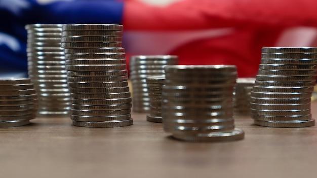 Американские монеты с флагом соединенных штатов америки. инвестиционная концепция, бизнес-финансы и экономия денег. монеты сша сложены на фоне американского флага. выборочный фокус.