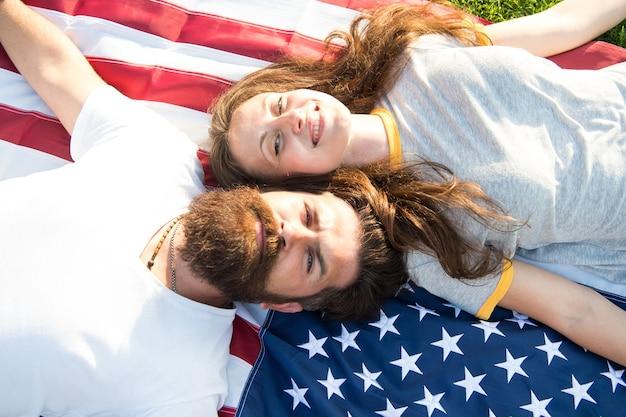 Американская пара расслабляющий на флаге сша на открытом воздухе. день независимости. национальный праздник. бородатый битник и влюбленная девушка. 4 июля. американская традиция. история америки. американский патриотический народ.