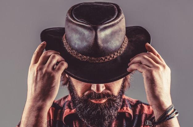 아메리칸 카우보이. 가죽 카우보이 모자. 카우보이 모자를 쓰고 젊은 남자의 초상화입니다. 카우보이 모자