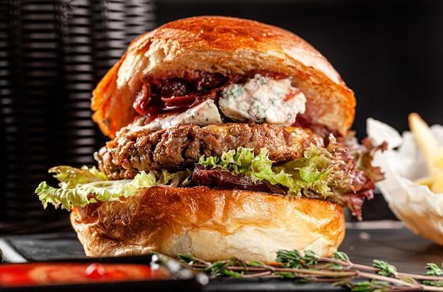 미국 요리 개념. 큰 돈까스가 들어간 육즙이 풍부한 고기 버거. 집에서 햄버거 요리하기. 레스토랑 또는 카페 메뉴의 배경 이미지입니다. 복사 공간