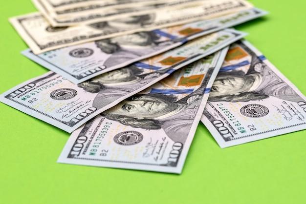 緑のテーブルに分離された米ドル紙幣