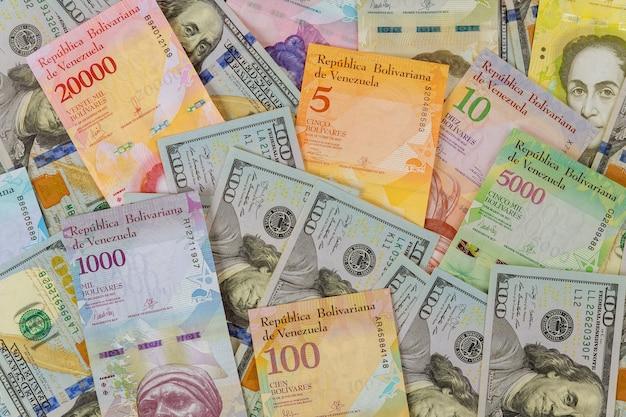Примечания американских долларовых банкнот над банкнотой венесуэльского боливара с бумажными счетами различной валюты.