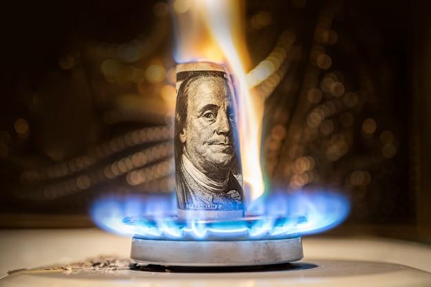 Американский доллар горит в огне. горящая газовая горелка на фоне ста долларов. понятие о подорожании газа в сша. дорогое газоснабжение