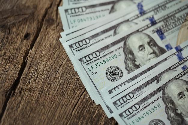 Американские долларовые банкноты распространяются на старый деревянный стол