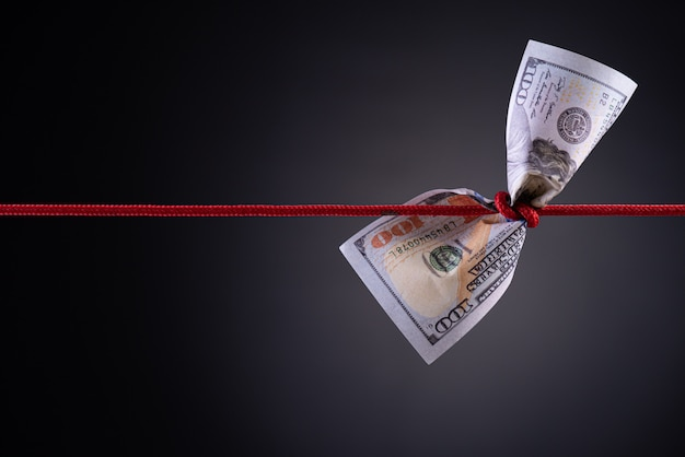 American dollar tied up in red rope knot on dark with copy space
