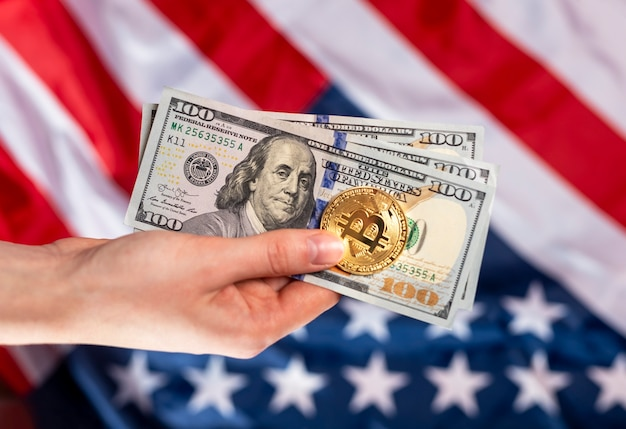 Банкноты американских долларов и монета биткойн в женских руках.