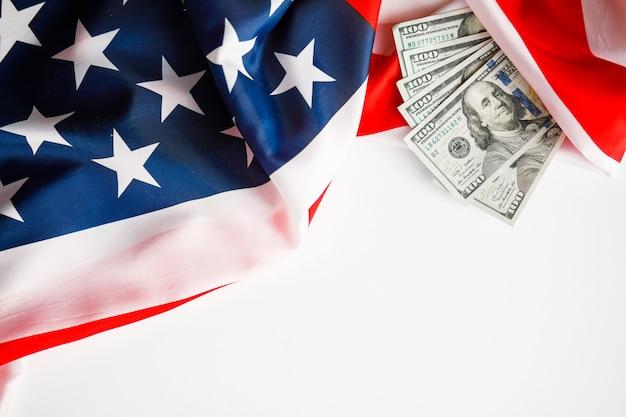 アメリカドルの現金。米国旗の背景に100ドル紙幣のクローズアップ
