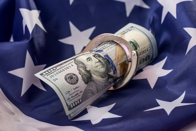 American dollars in handcuffs on national flag