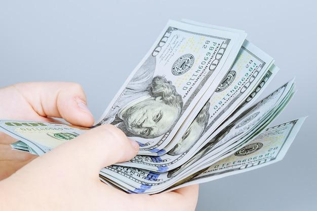 灰色の背景に米ドル。 100ドル札を数えます。