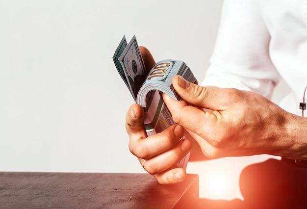 Американские доллары или доллары сша. рука, считающая сто американских денег или 100 долларовую купюру.