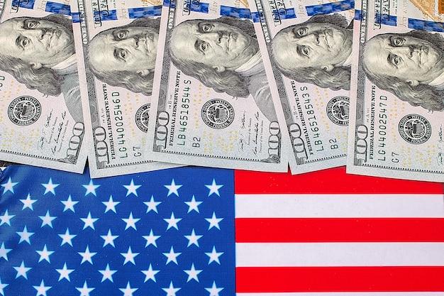 米国の旗の上のアメリカのドル