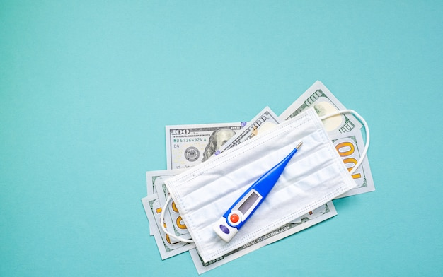 American dollars and a protective mask with a thermometer