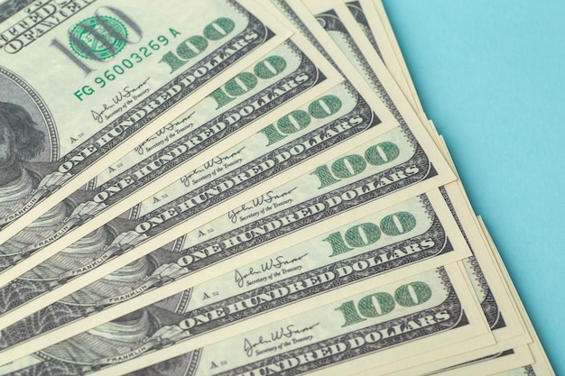 American dollars on the table. one hundred (100) dollars laid out on a blue background. american currency and economy, exchange rates, international economy and market concept
