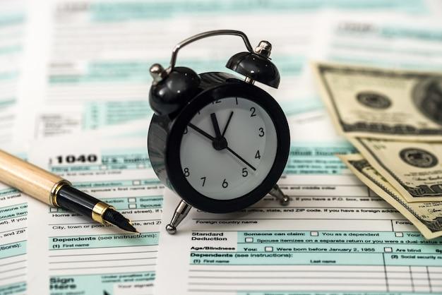 개별 세금 양식 위에 시계가 있는 미국 달러