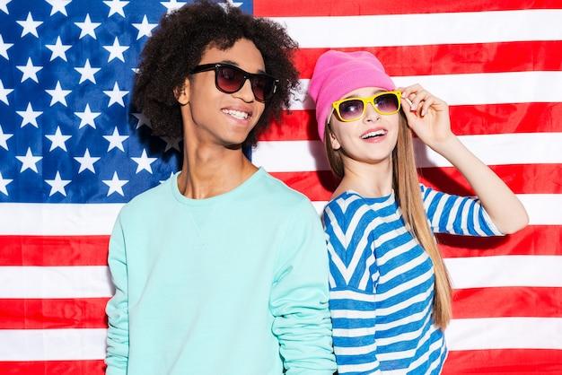 アメリカの夢。サングラスをかけ、アメリカの国旗に立って笑っているファンキーな若いカップル