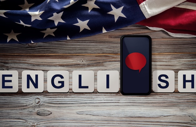 American english language concept. mobile phone with speech bubble and usa flag lay on vintage wooden background. online learning. speak english. top view