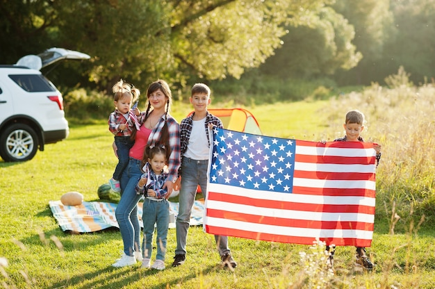 미국 가족. 엄마와 네 아이. 미국 국기와 함께. 축하하는 미국.