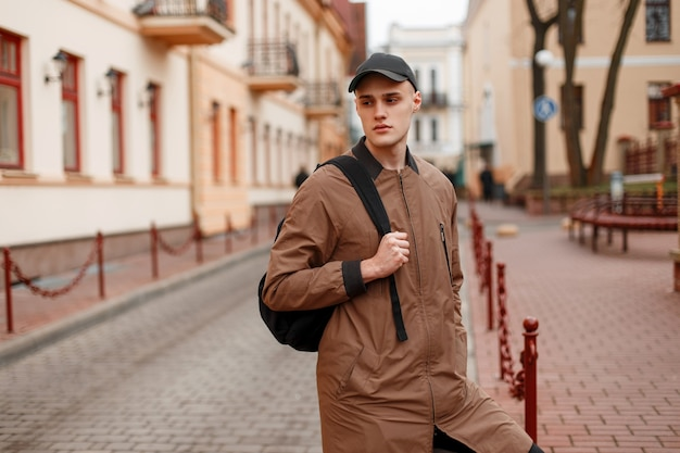 American fashionable handsome young man in a stylish beige long jacket in a stylish cap with a black backpack walks through the city on a spring day
