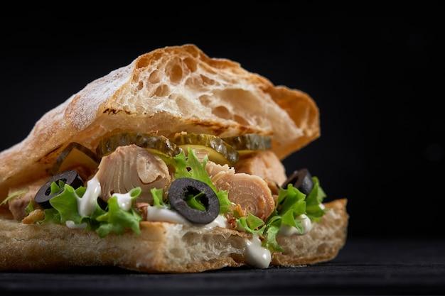 アメリカのファーストフード。ジューシーなマグロのサンドイッチ、チーズ、サラダ、オリーブ、暗い空間で。クラブフード。