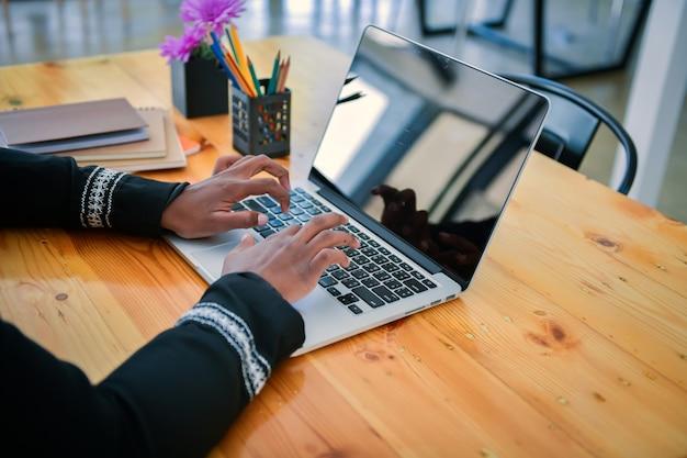 미국 여성 사업가 아프리카계 미국인이 사무실에서 일하기 위해 노트북을 사용합니다.