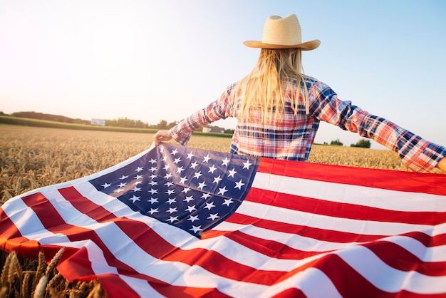 American female farmer in casual clothing with arms spread open holding usa flag in wheat field
