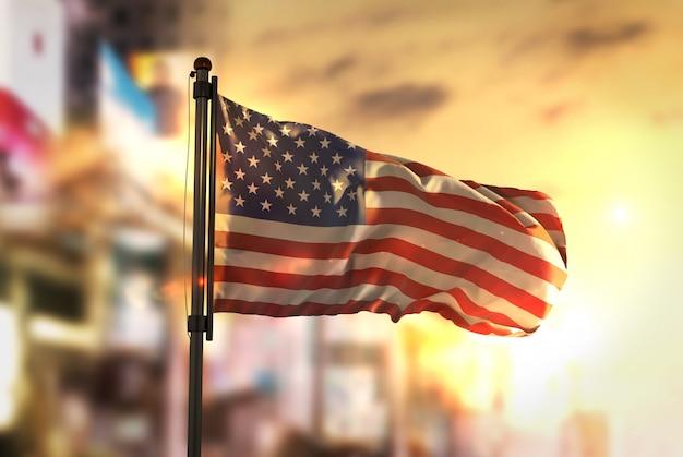 American flag against city blurred background at sunrise backlight