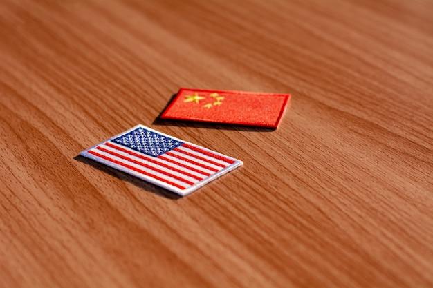 나무 책상에 미국 국기와 중국 국기입니다.