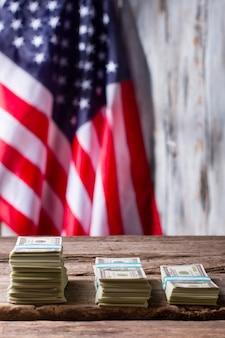 Американский флаг и долларовые пачки. стеки наличных денег рядом с флагом. годовая зарплата выросла. доход среднестатистического гражданина.