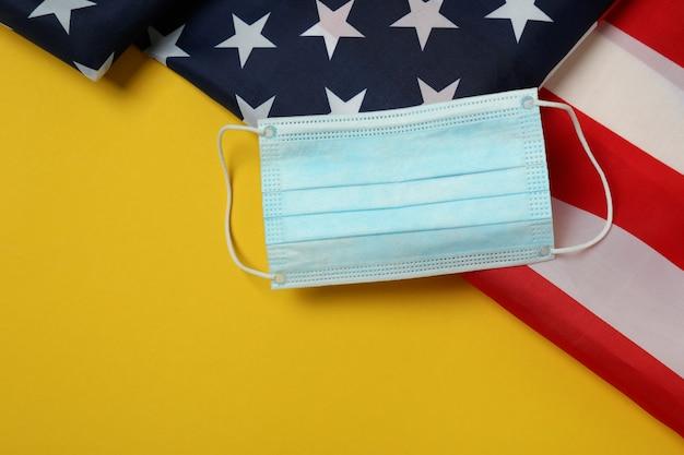 Американский флаг и маска на желтом