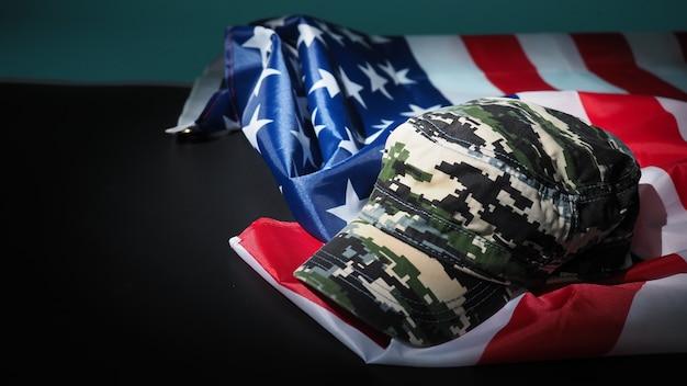 Американский флаг и военная шляпа или сумка. угол обзора сверху. солдатская шляпа или шлем с национальным американским флагом на черном фоне. представьте военную концепцию камуфляжным объектом и национальным флагом сша.