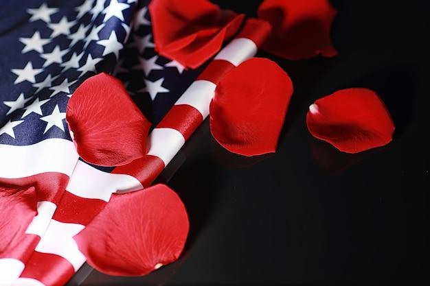 테이블에 미국 국기와 장미 꽃입니다. 아메리카 합중국의 상징과 붉은 꽃잎. 애국심과 기억.