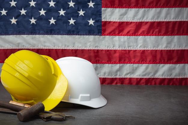 アメリカの国旗とヘルメット労働者の日のコンセプトに近いツール。