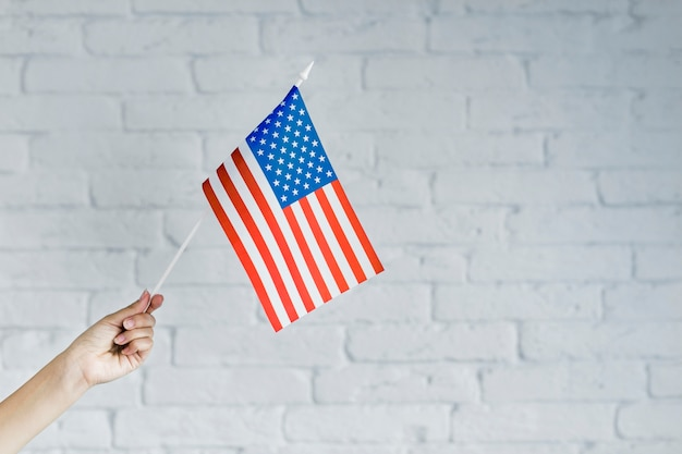 American flag background with hand holding flag