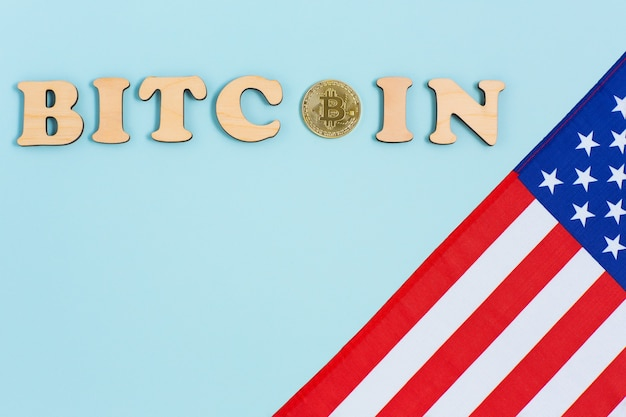 American flag, bitcoin and wooden letters on blue surface