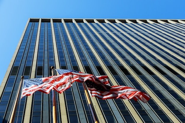American flag blowing in the wind against commercial building with windows and blue sky