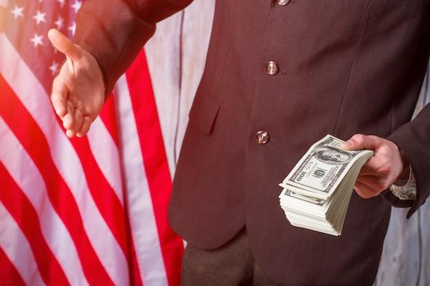 Американский флаг, бизнесмен и наличные деньги. человек с деньгами протягивает руку. мы ценим каждого союзника. начало рабочего дня мэра.
