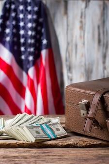 Американский флаг, футляр и доллары. коричневый чемодан рядом с пачками наличных. успех и патриотизм. месячная зарплата сенатора.