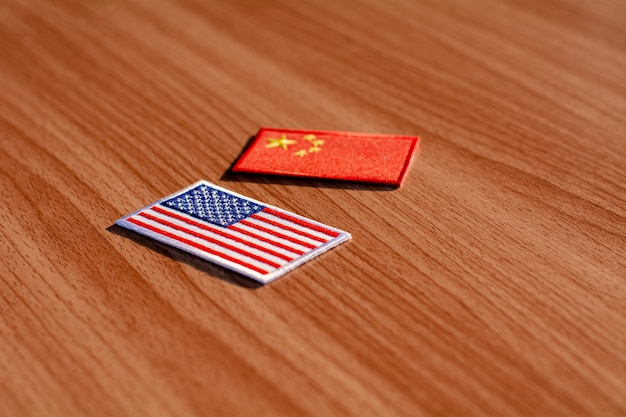 American flag and china flag on wooden desk.