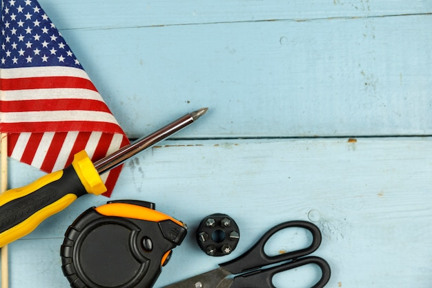 American flag and construction tools on blue wooden background with copy space
